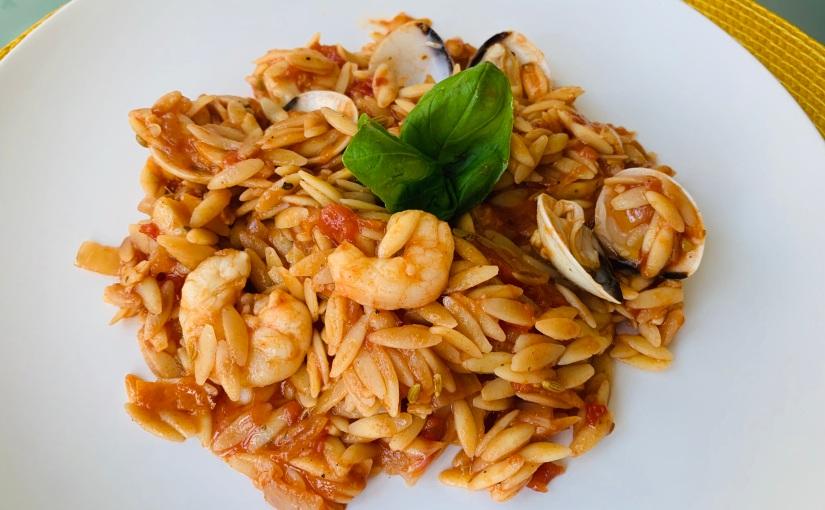 Orzo (pasta con forma de arroz) con salsa de tomate ylangostinos